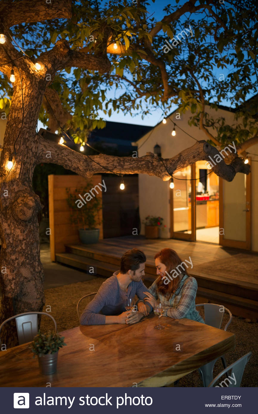 Affectionate couple drinking wine at patio table - Stock Image