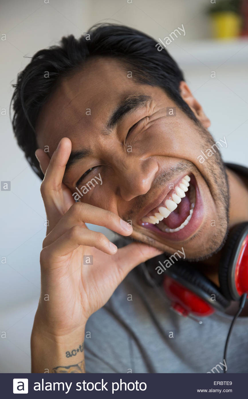 Portrait enthusiastic man with headphones laughing - Stock Image