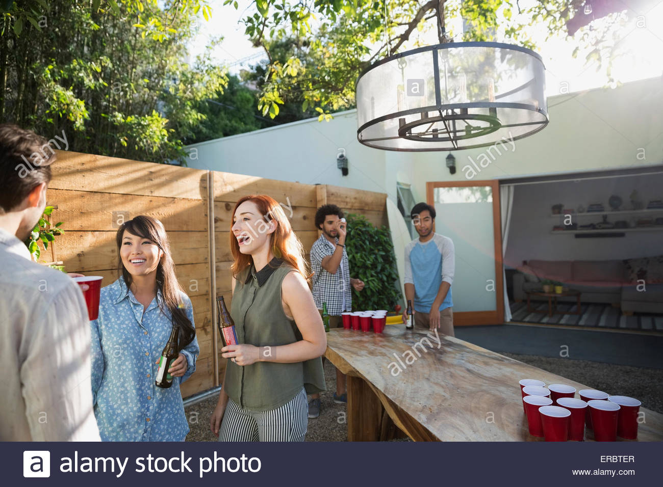Friends talking playing beer pong on sunny patio - Stock Image