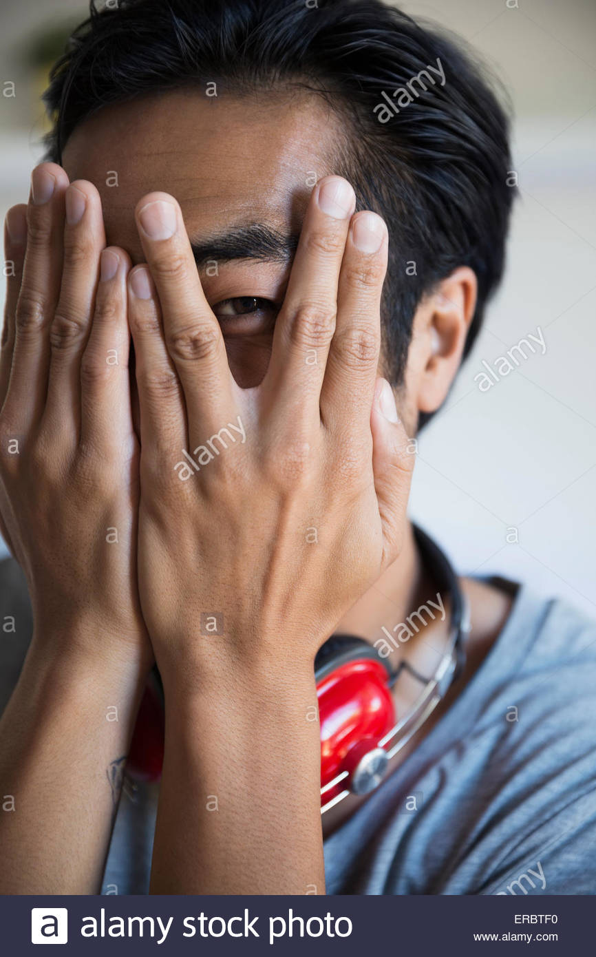 Close up portrait man peering through fingers - Stock Image