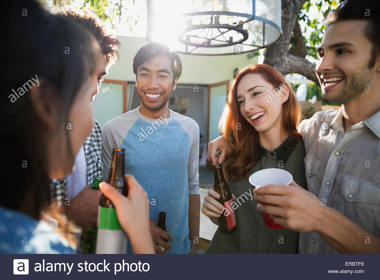 Smiling friends talking drinking beer on sunny patio - Stock Image