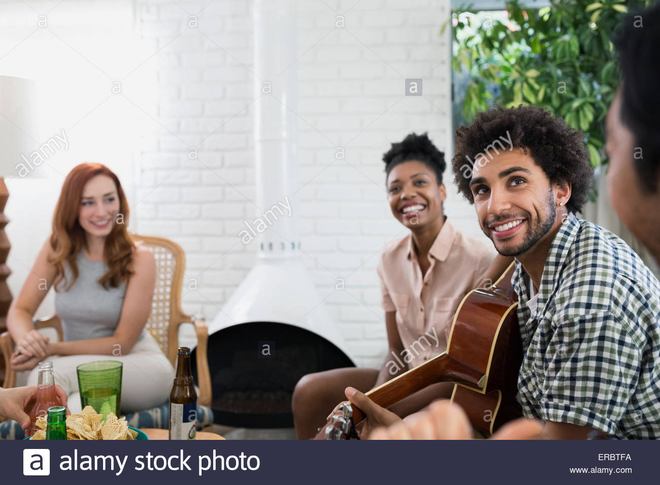 Friends hanging out playing guitar in living room Stock Photo