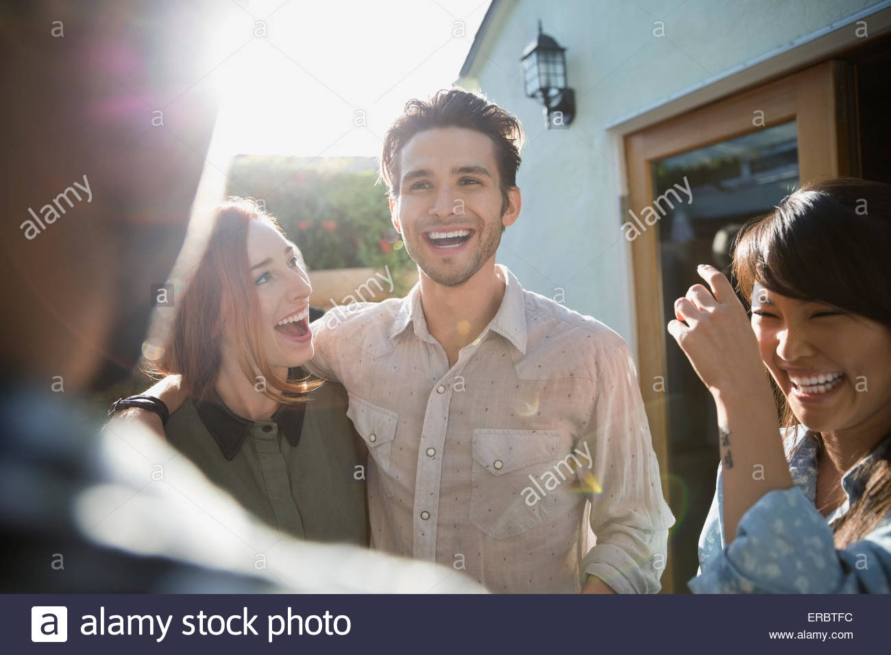 Friends laughing on sunny patio - Stock Image