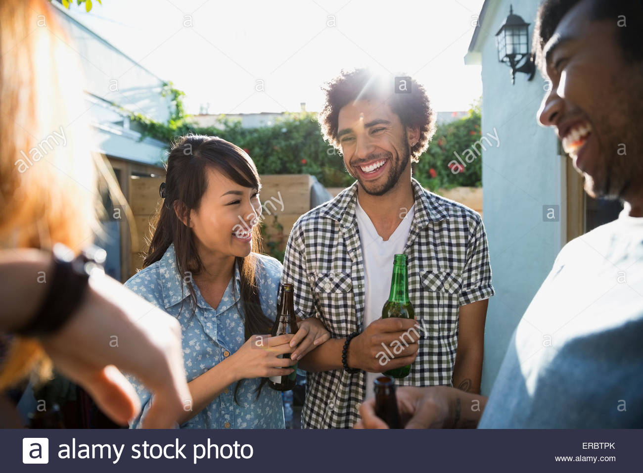 Laughing friends drinking beer on sunny patio - Stock Image