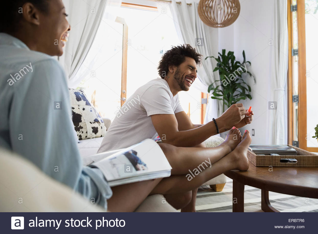 Laughing man giving girlfriend pedicure in living room - Stock Image