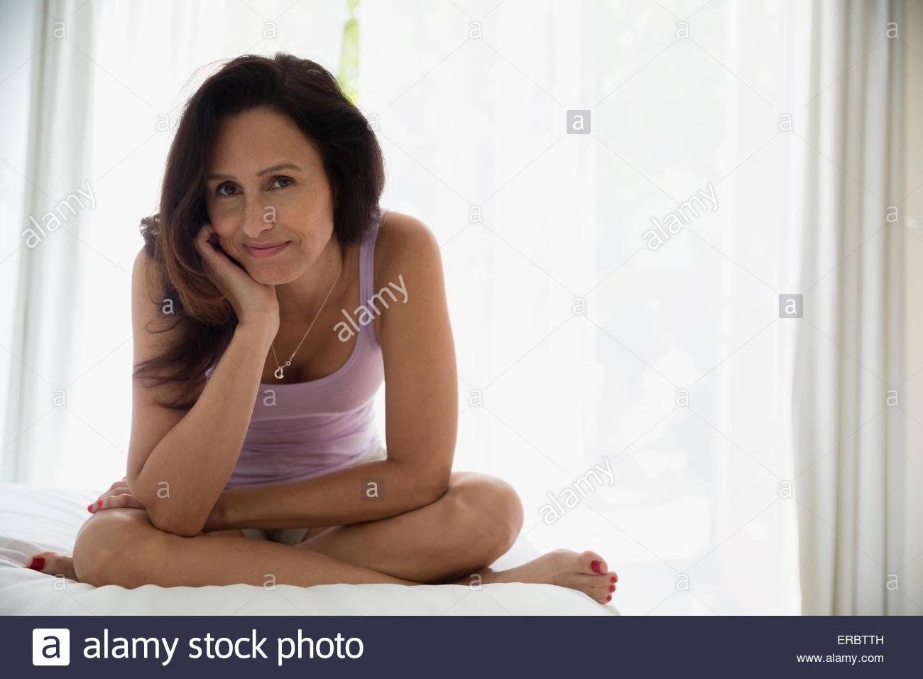 Portrait smiling brunette woman cross-legged in bedroom - Stock Image
