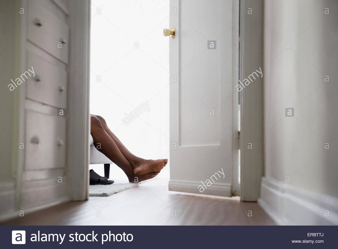 Bare feet of man in bedroom doorway - Stock Image