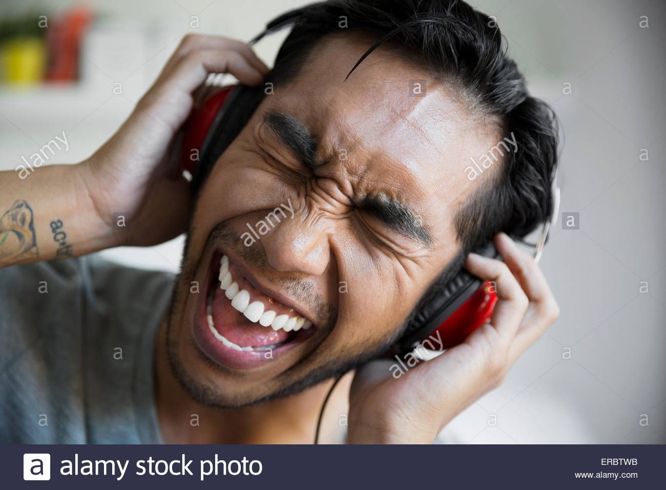 Enthusiastic man listening singing to music on headphones - Stock Image