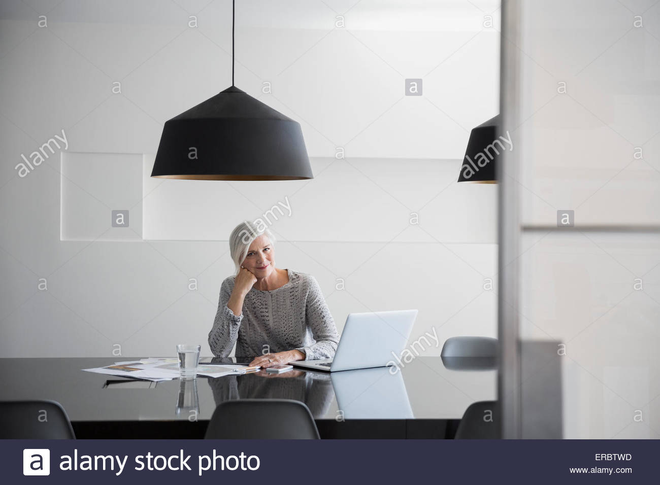Portrait designer with plans at laptop conference room - Stock Image