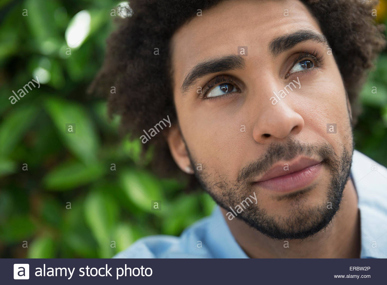 Close up portrait pensive man looking up - Stock Image