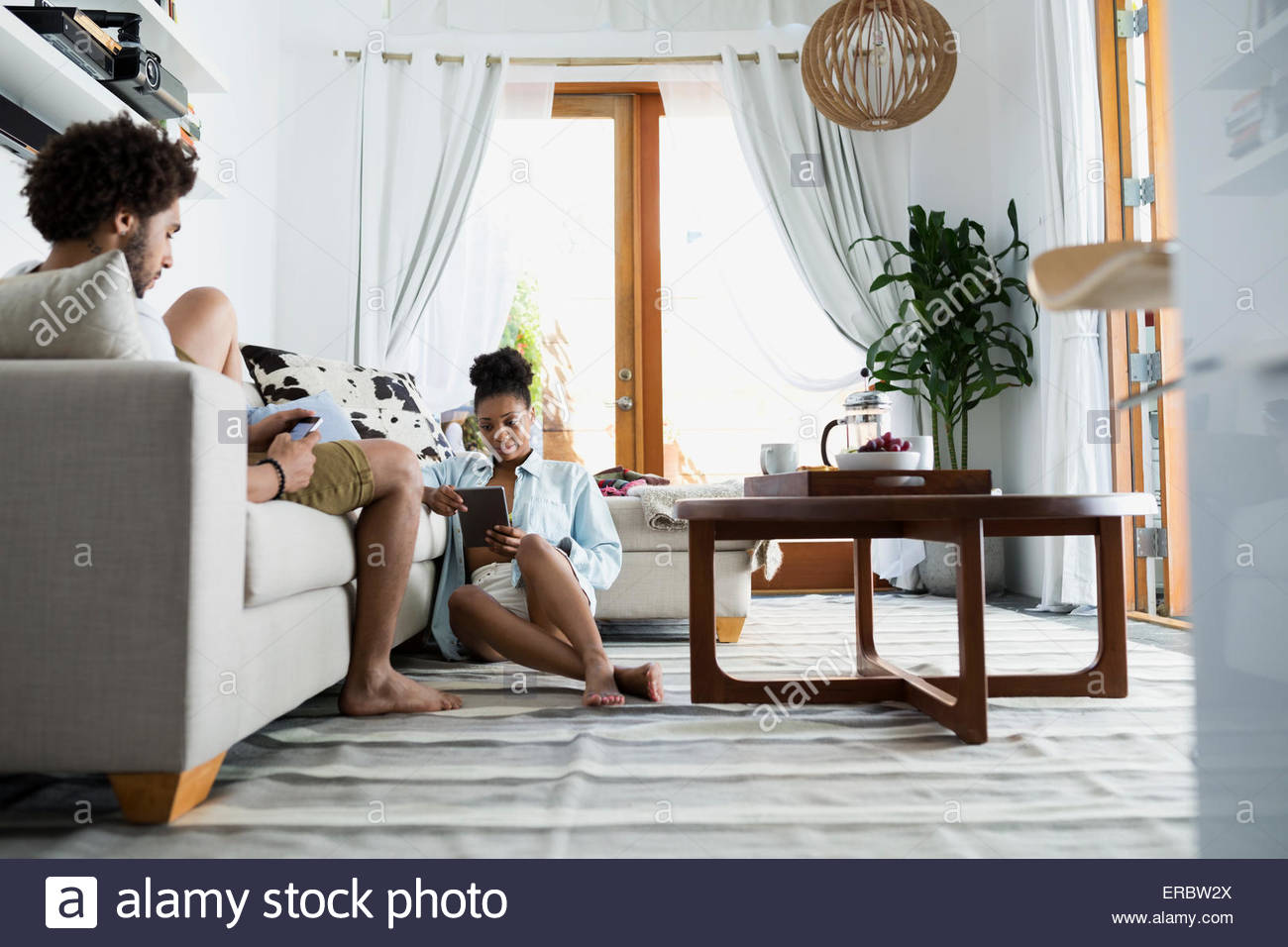 Couple relaxing with technology in living room - Stock Image