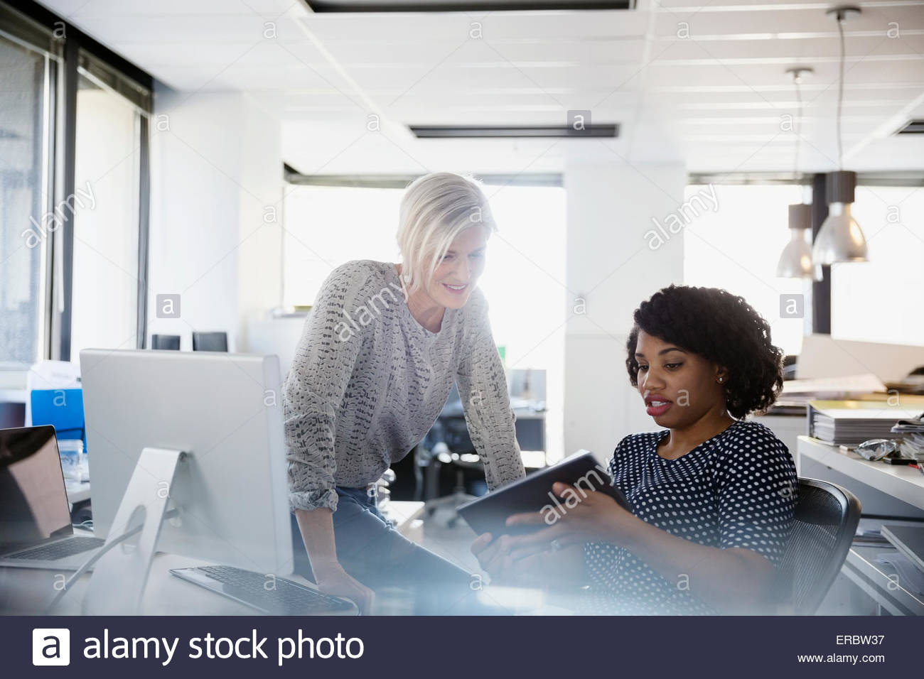 Businesswomen working at digital tablet in office - Stock Image