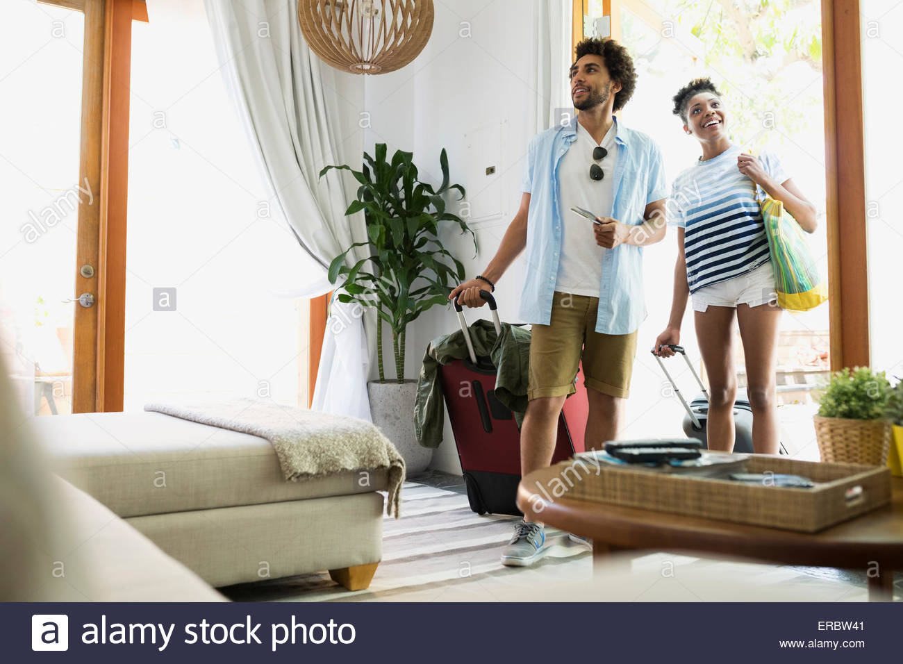 Couple with suitcases arriving at vacation house - Stock Image