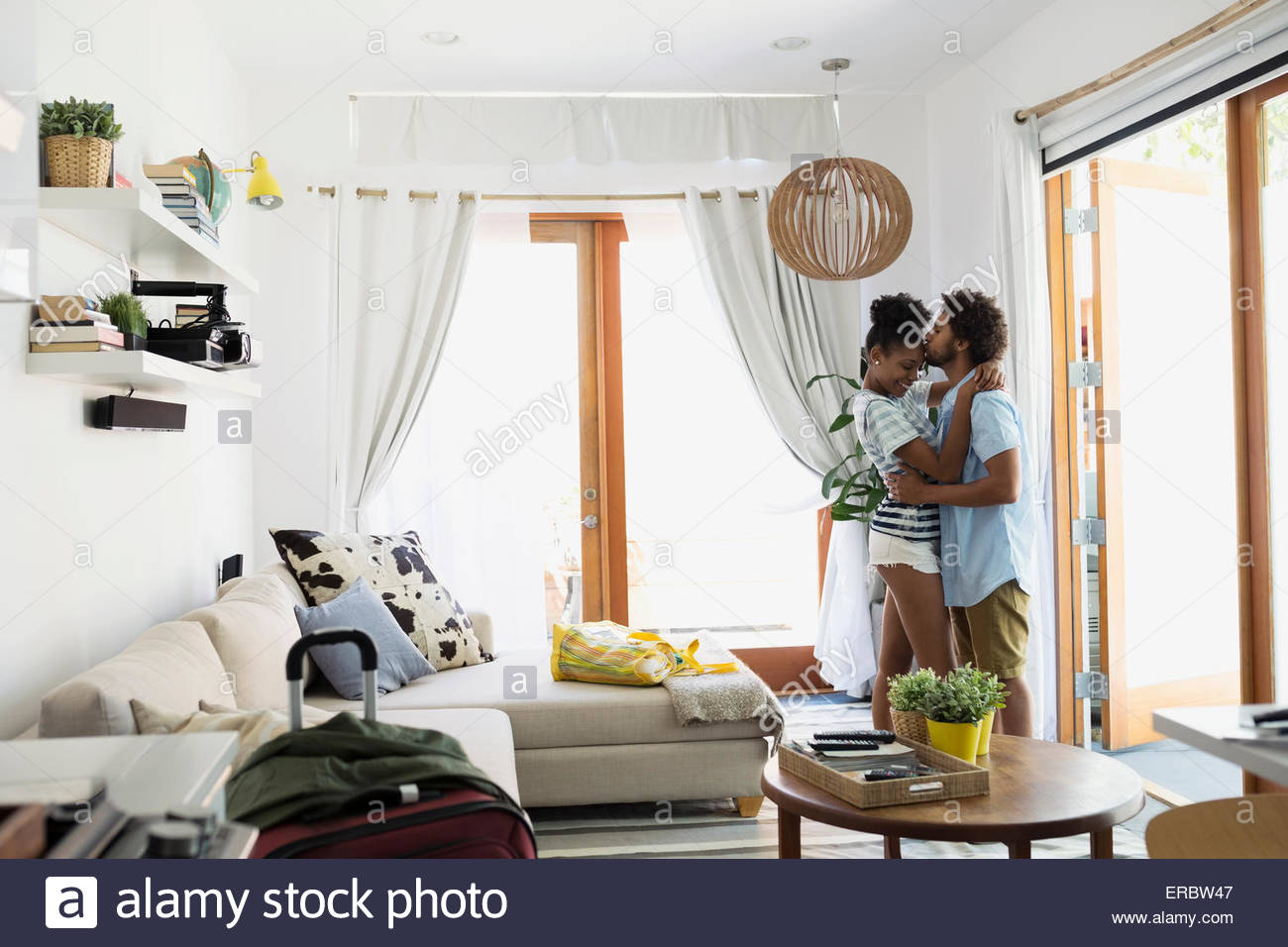 Couple hugging and kissing vacation house living room - Stock Image
