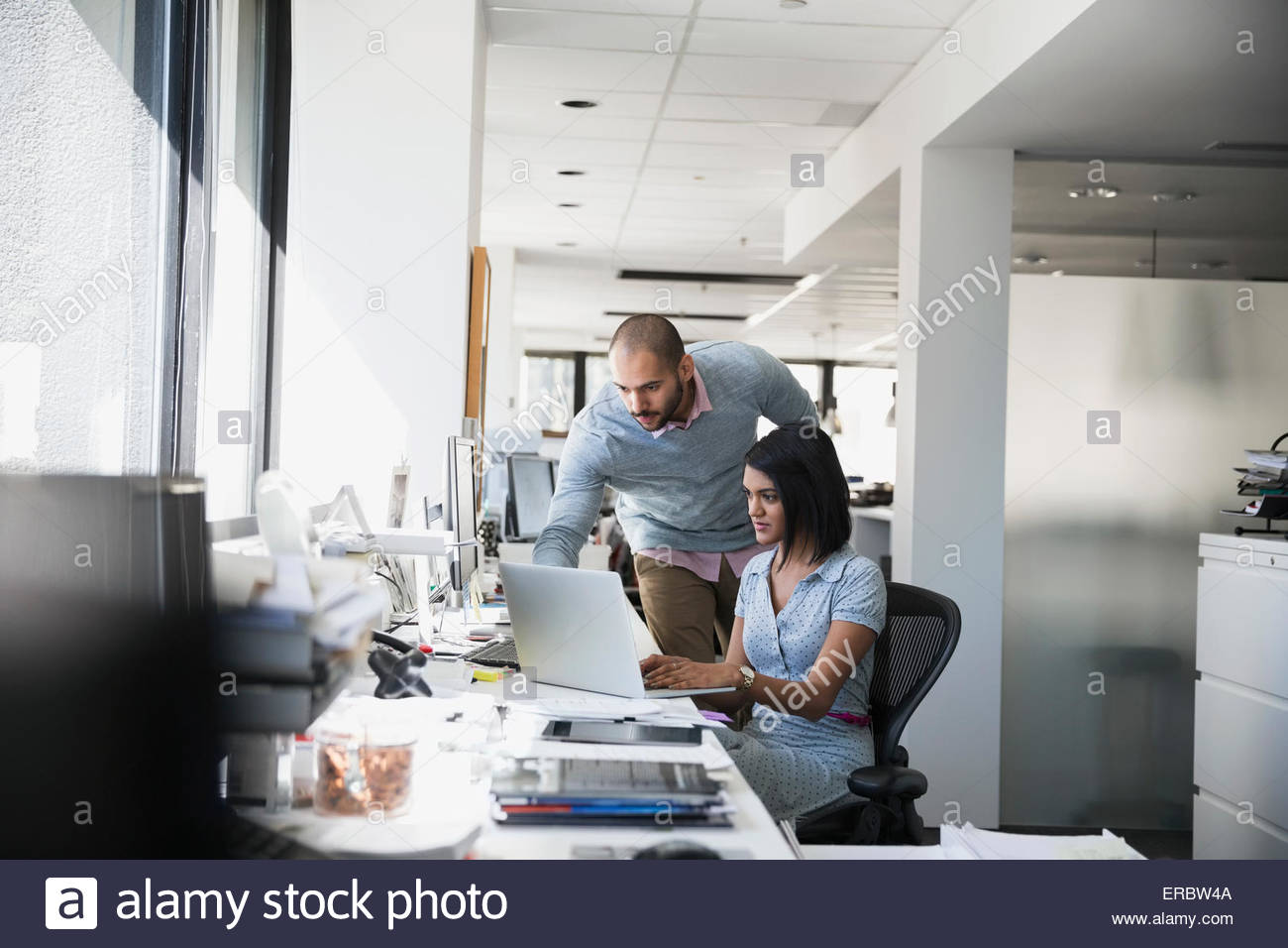 Businessman and businesswoman working at laptop in office - Stock Image