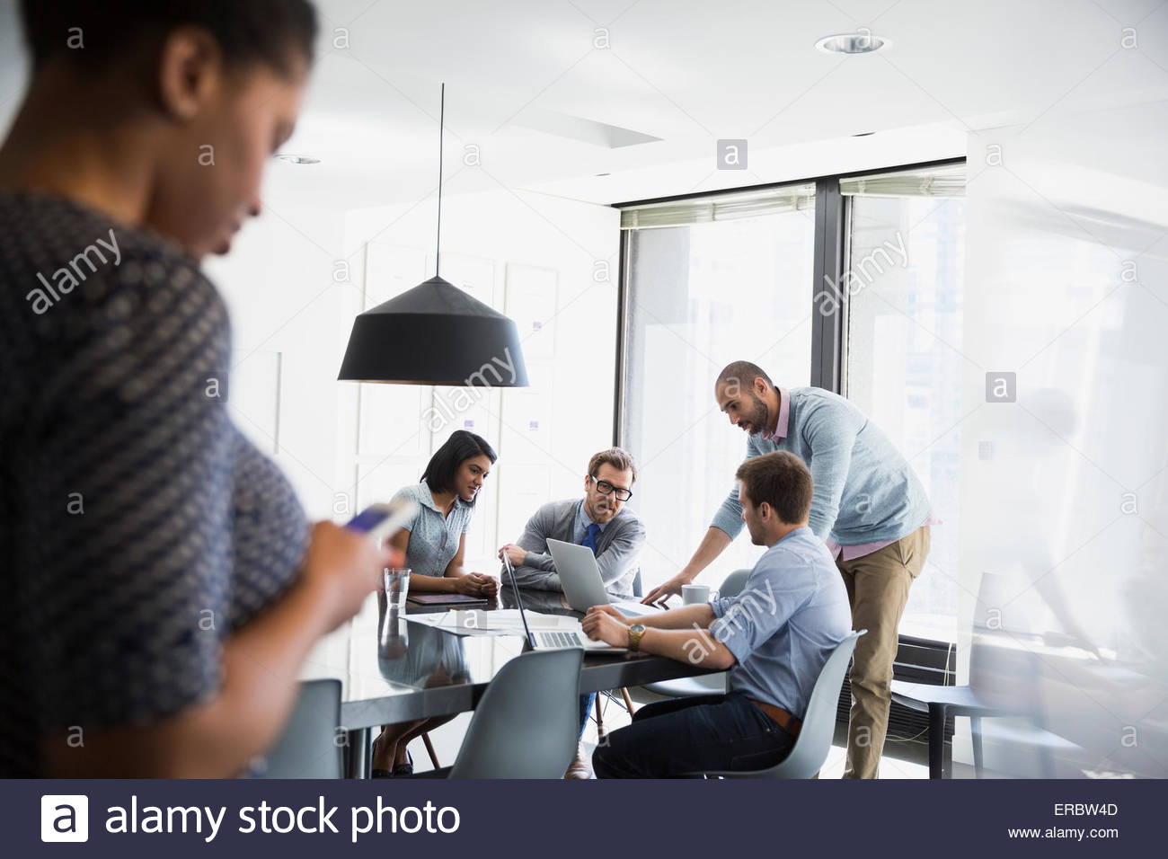 Business people working at laptop conference room meeting - Stock Image