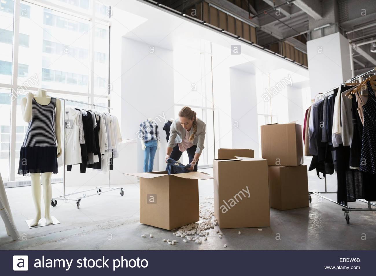 Fashion stylist unpacking clothing in studio - Stock Image