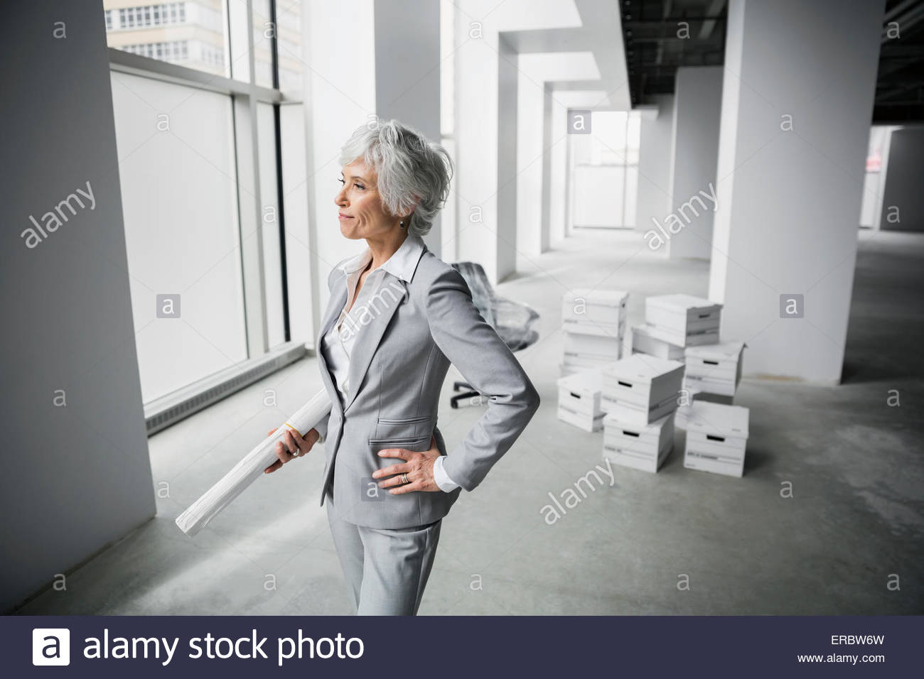 Confident architect with blueprints in new office - Stock Image