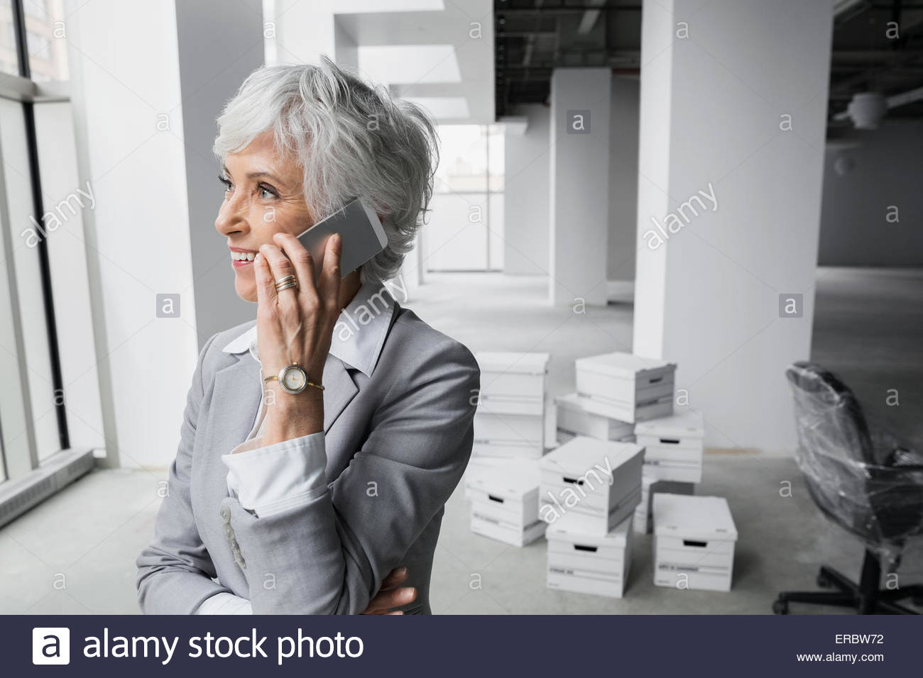 Businesswoman talking on cell phone in new office - Stock Image