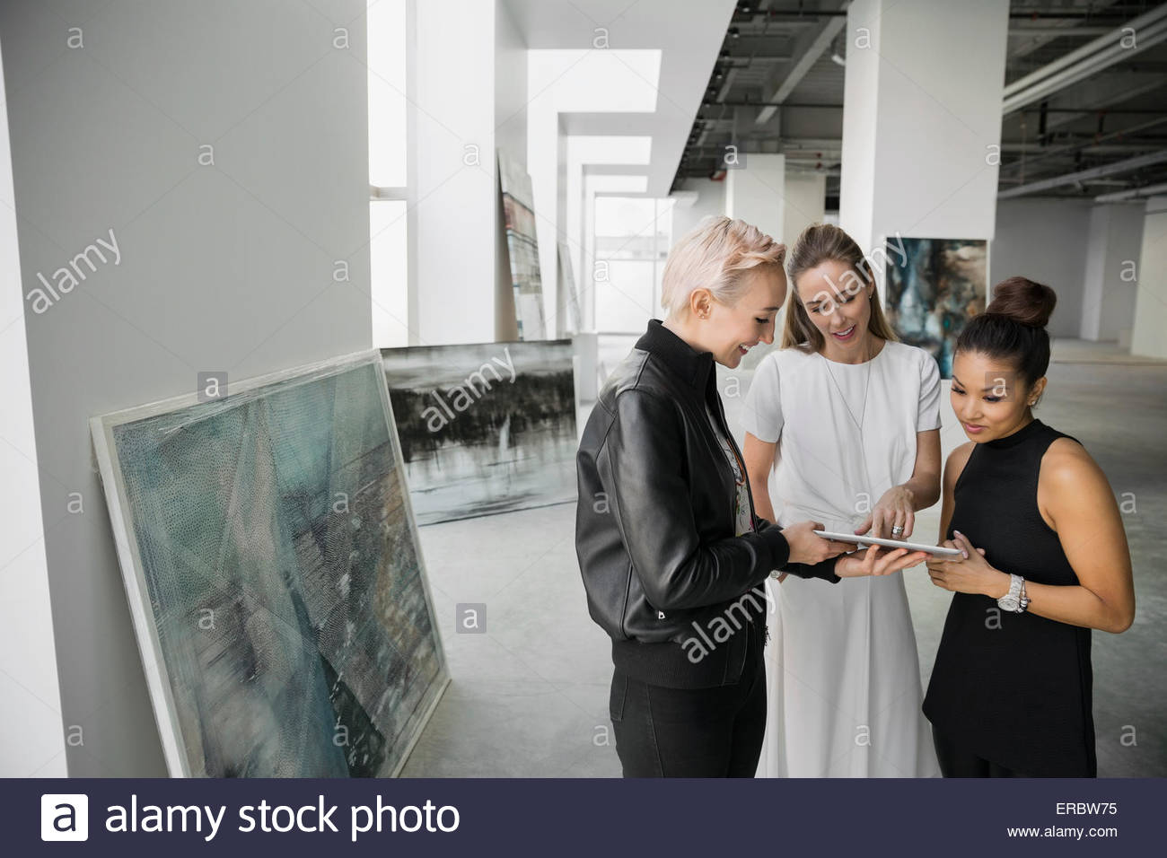 Artist and art dealers using digital tablet gallery - Stock Image