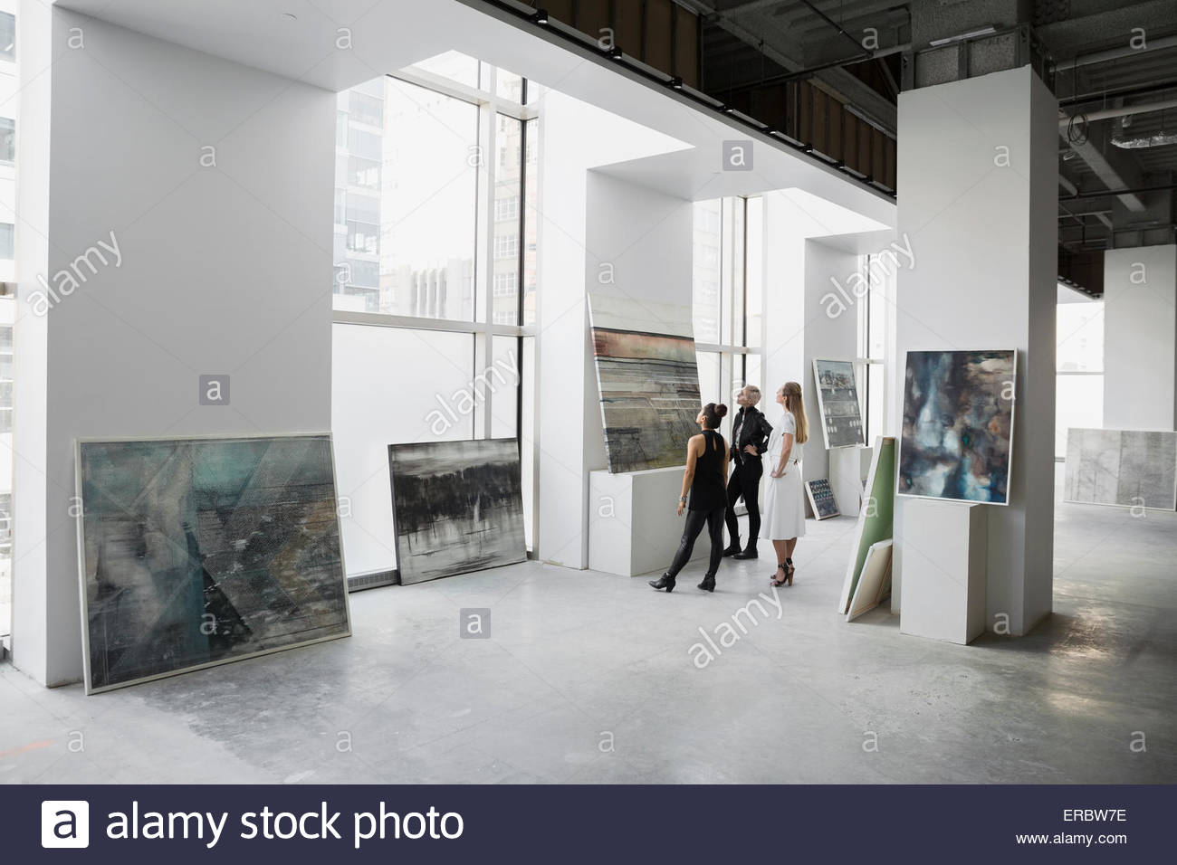 Art dealers examining painting in art gallery - Stock Image