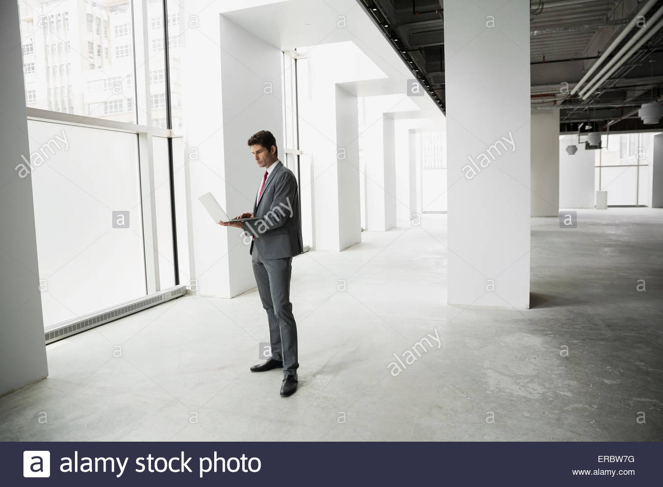Businessman using laptop in empty office - Stock Image