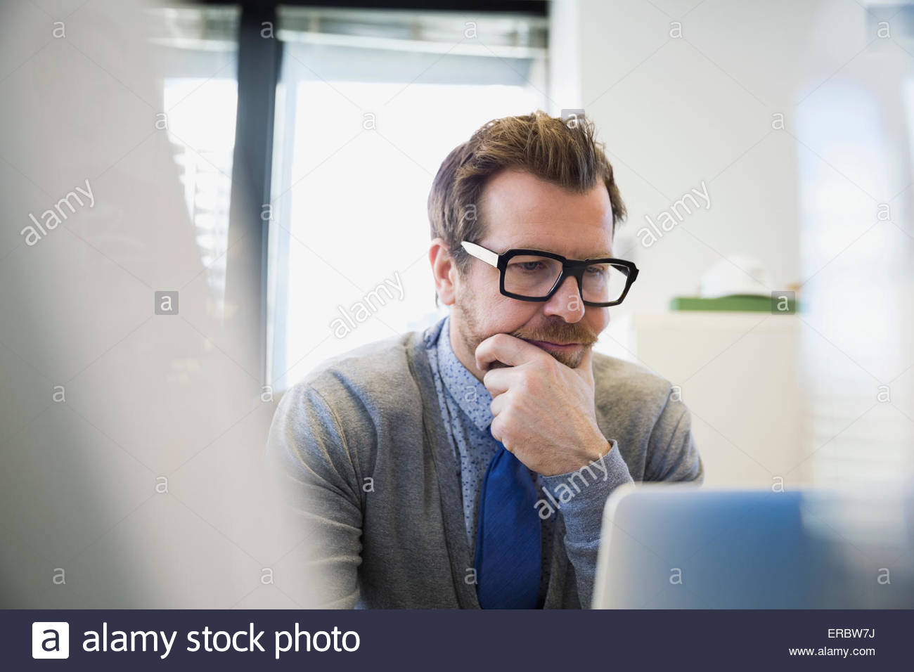 Focused businessman working at laptop hand on chin - Stock Image