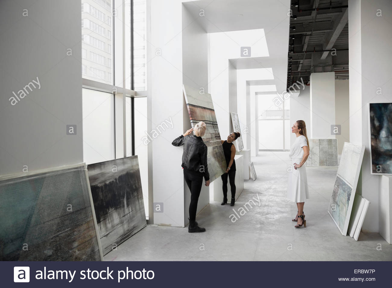 Art dealers hanging painting on gallery wall - Stock Image