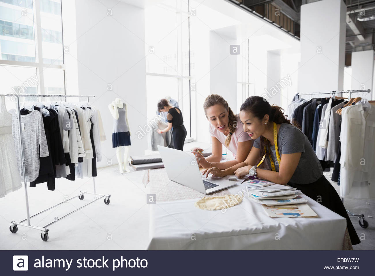 Fashion designers at laptop with sewing patterns - Stock Image