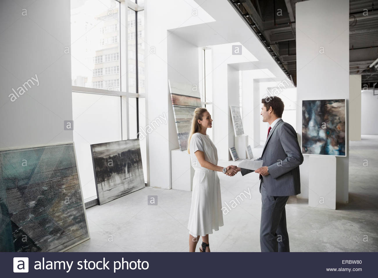 Art dealer and businessman handshaking in art gallery - Stock Image