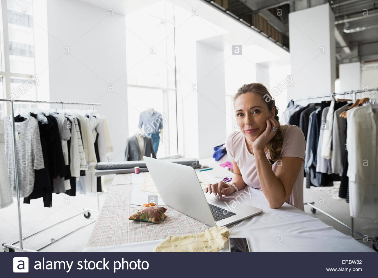 Portrait confident fashion designer using laptop sewing patterns - Stock Image