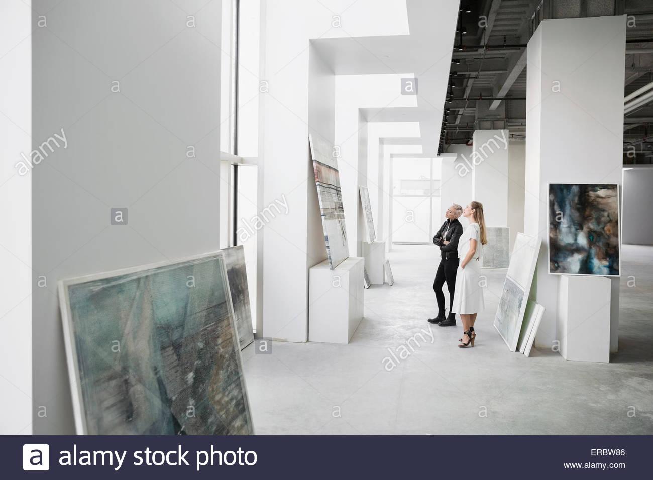 Art dealers examining painting in art gallery - Stock Image