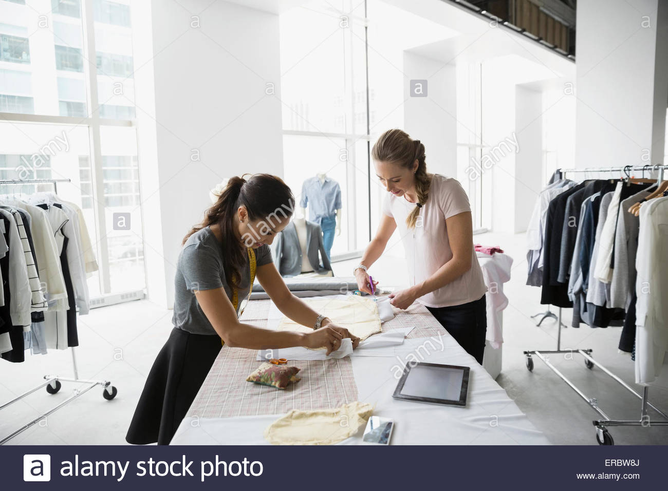 Fashion designers working with fabric and sewing patterns - Stock Image