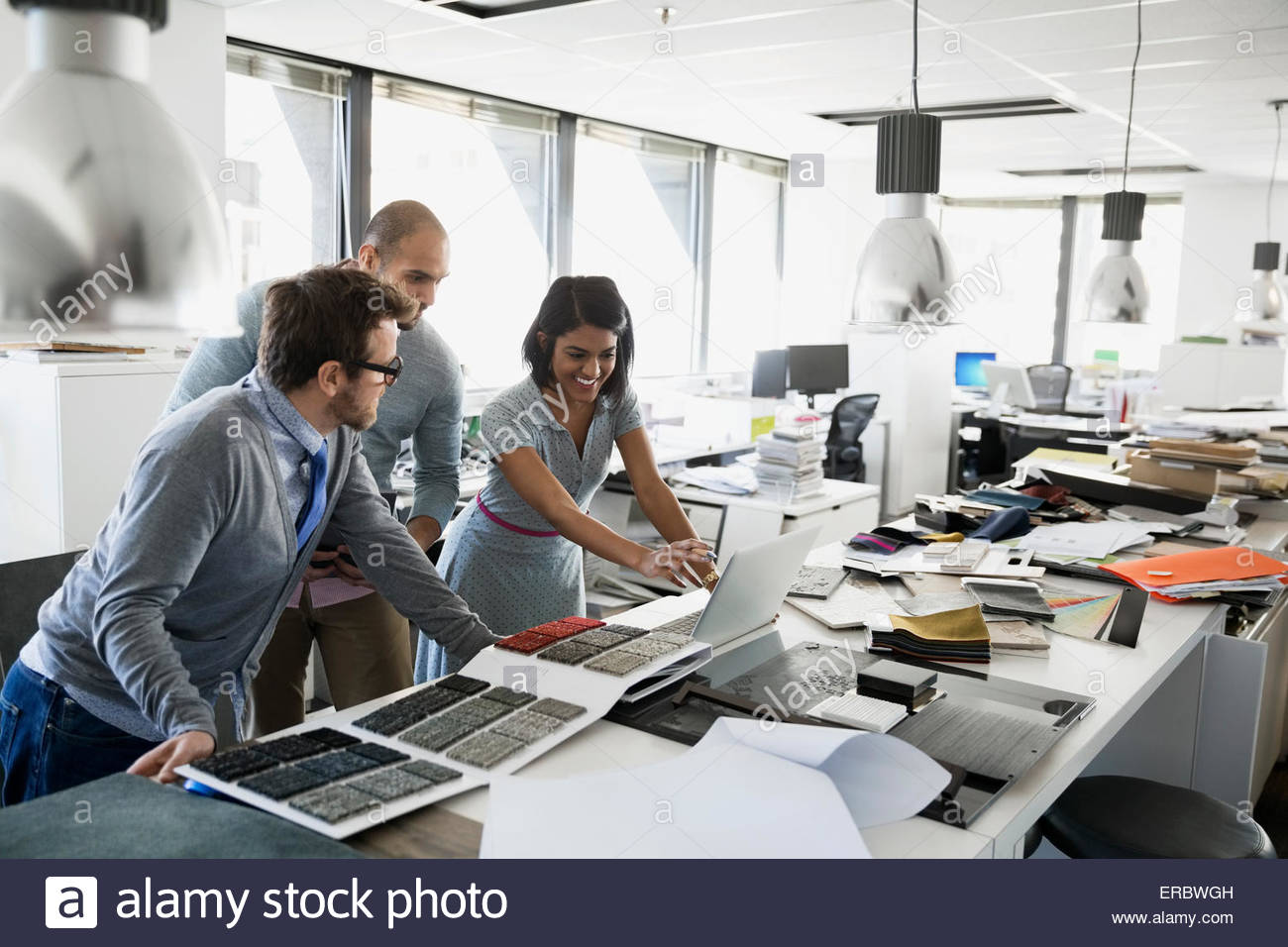 Interior designers with swatches working at laptop - Stock Image