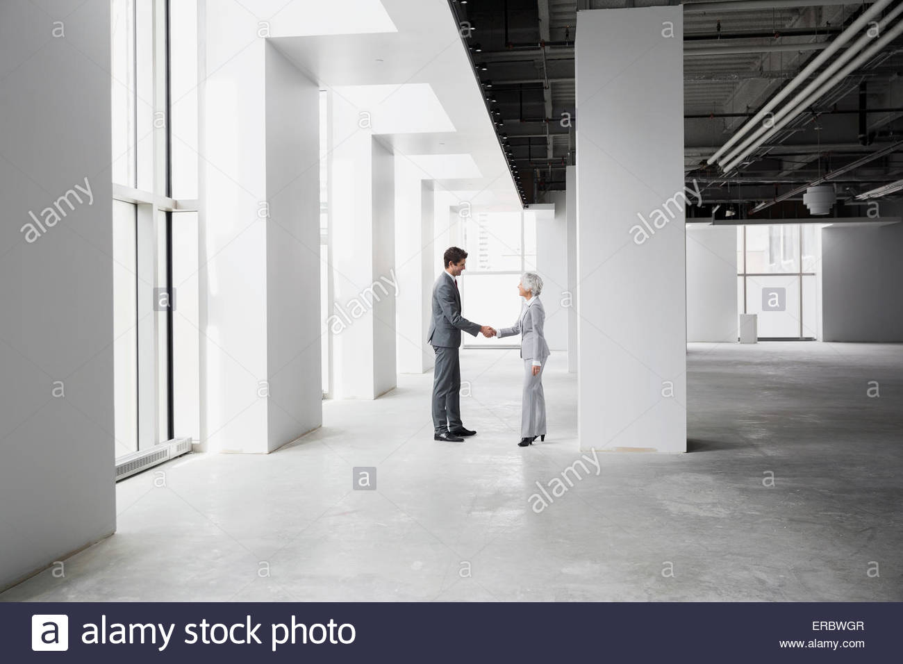 Businessman and businesswoman handshaking in empty office - Stock Image
