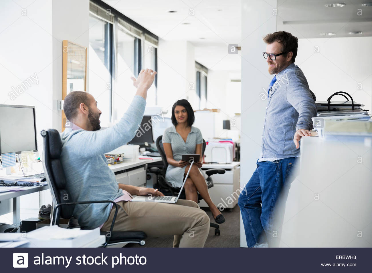 Businessman gesturing and explaining to co-workers office - Stock Image