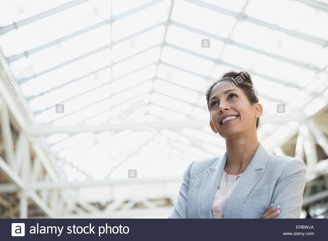 Portrait of smiling woman looking up in atrium - Stock Image