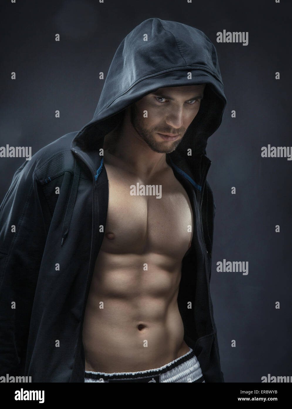 Muscular and handsome athlete making the muscles - Stock Image