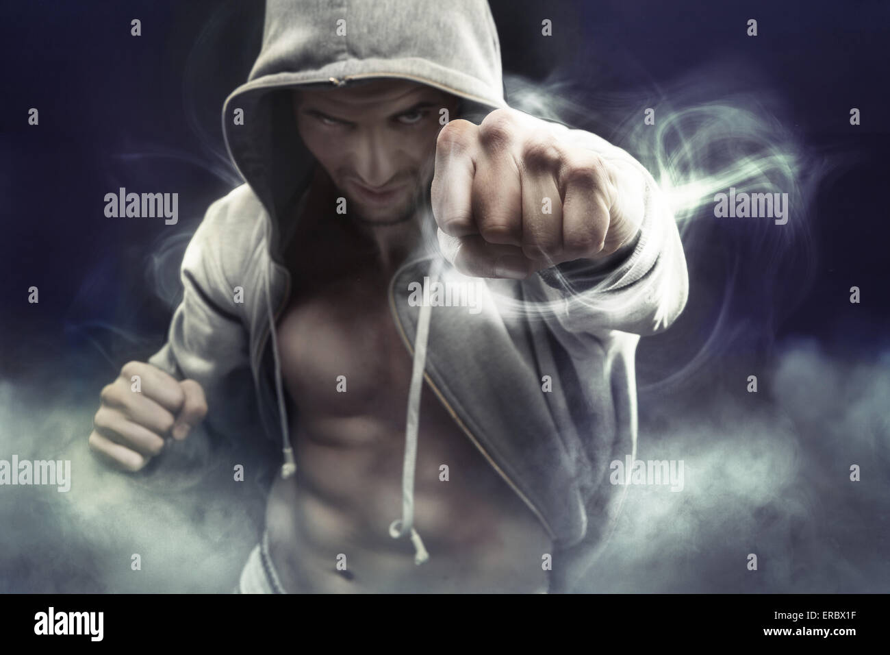 Hooded muscular boxer punching an enemy - Stock Image