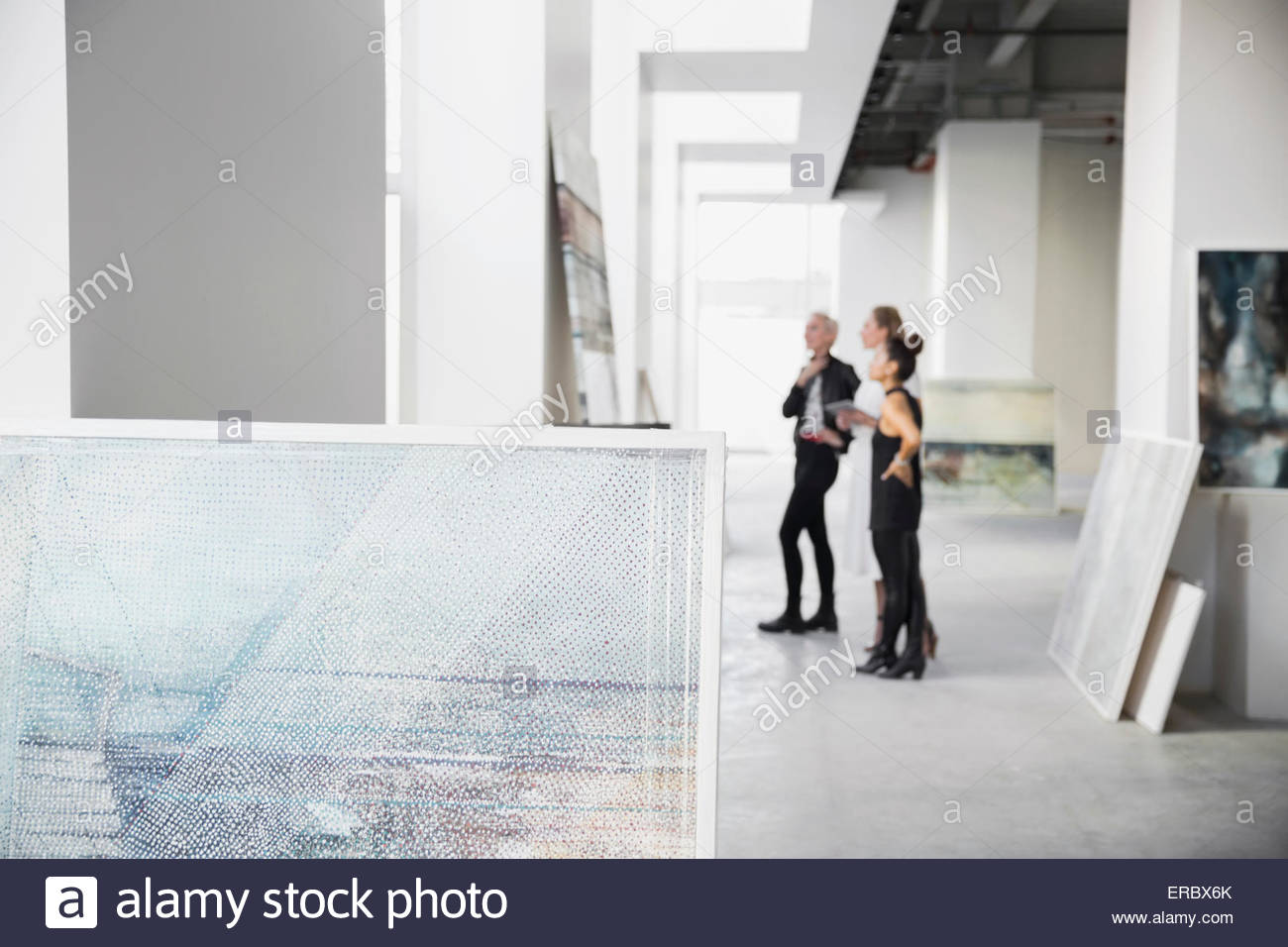 Artist and art dealers examining paintings art gallery - Stock Image