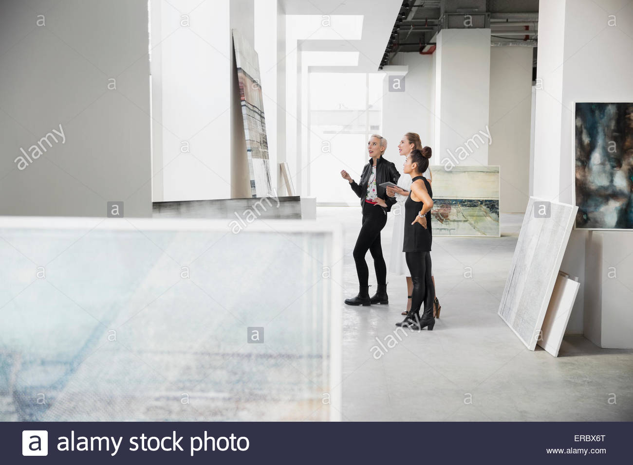 Artist and art dealers discussing paintings art gallery - Stock Image