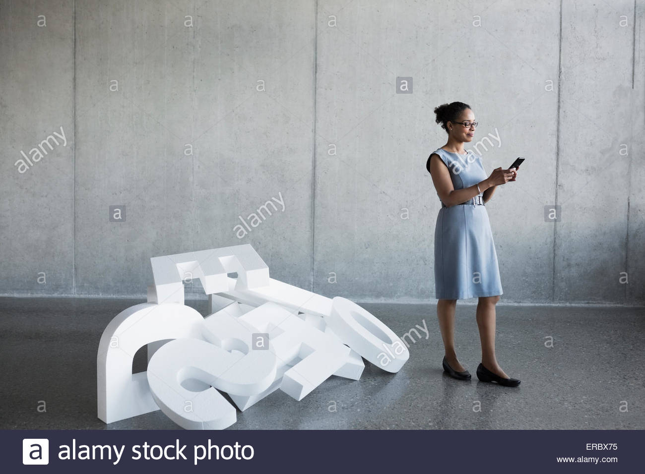 Businesswoman texting on cell phone near fallen letters - Stock Image
