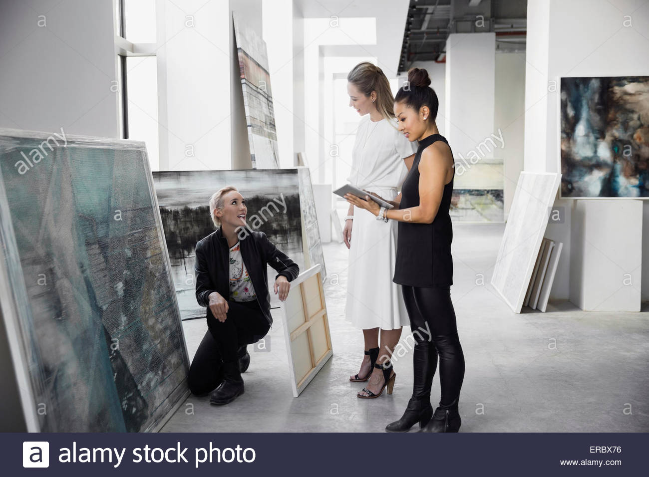 Artist and art dealers with paintings digital tablet - Stock Image