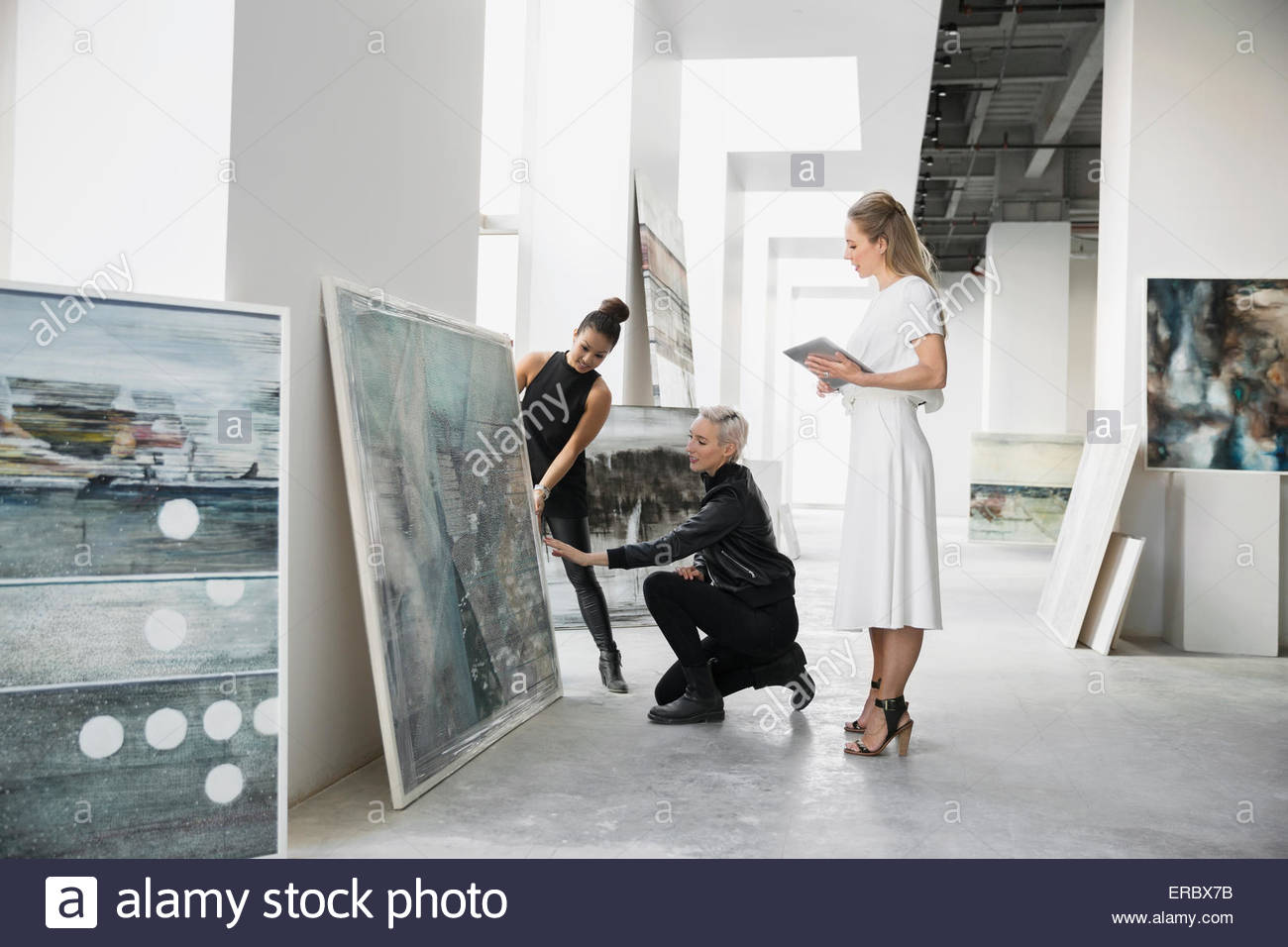 Artist and art dealers discussing paintings digital tablet - Stock Image
