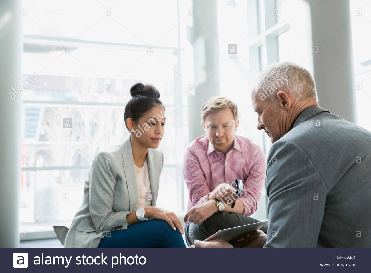 Business people using digital tablet in lobby - Stock Image