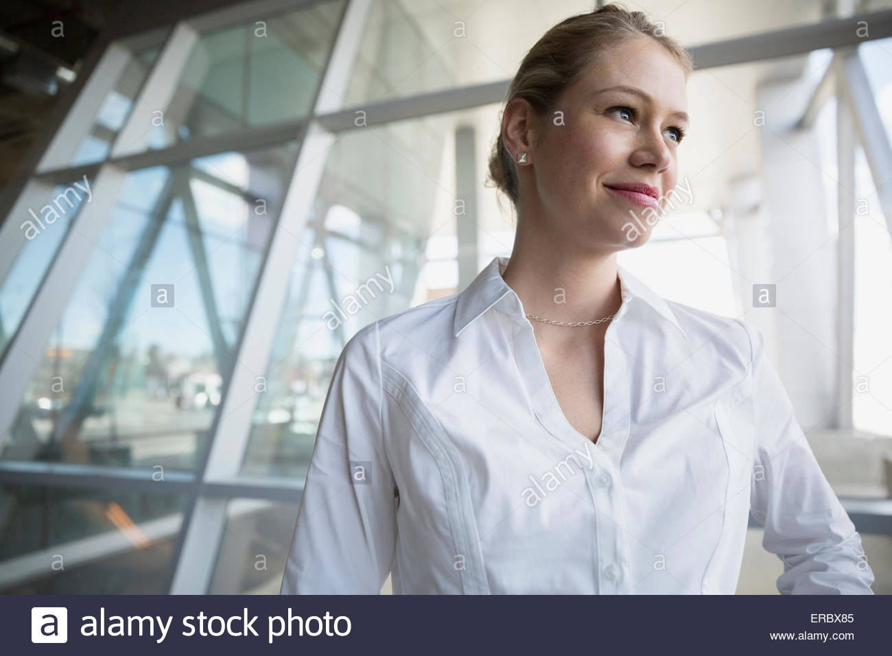 Smiling blonde businesswoman with blonde hair looking away - Stock Image