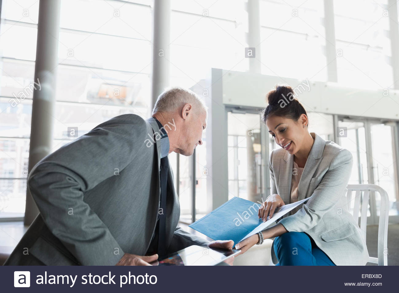 Business people reviewing paperwork in lobby - Stock Image