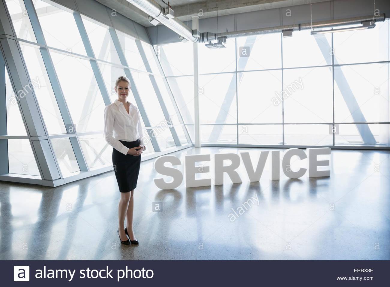 Portrait confident businesswoman near 'Service' letters - Stock Image