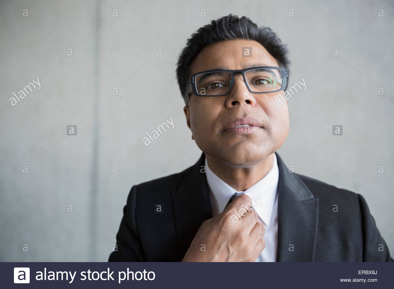Portrait businessman with black hair adjusting tie - Stock Image