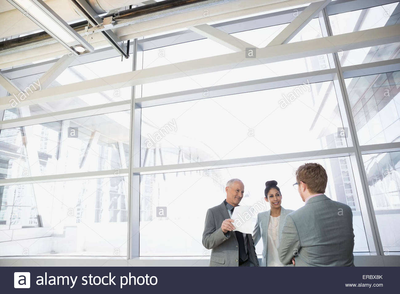 Business people talking in modern lobby - Stock Image